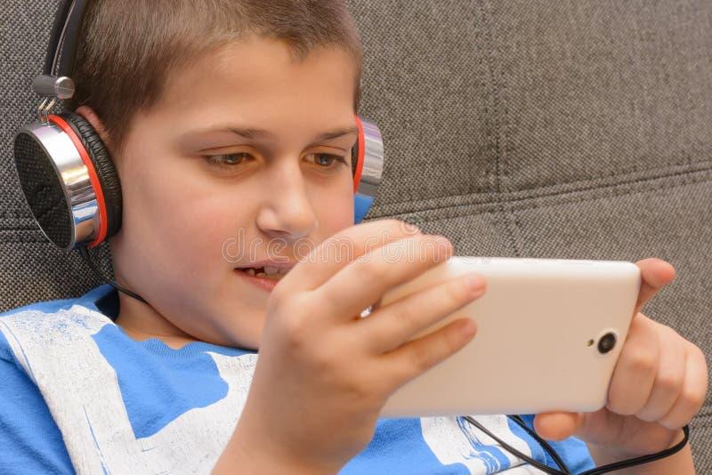 有耳机和手机的男孩在手中 库存照片