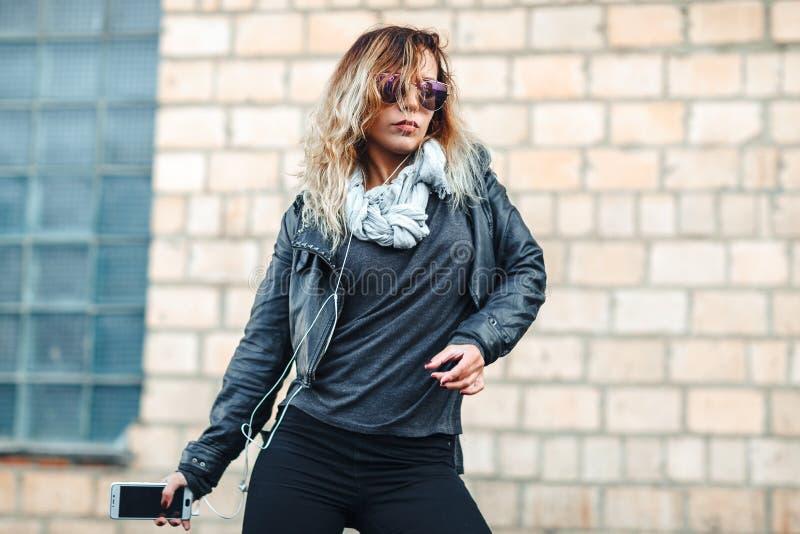 有耳机和智能手机的年轻美丽的性感的妇女在手中在被反映的太阳镜,黑皮夹克,黑牛仔裤danc 免版税库存照片