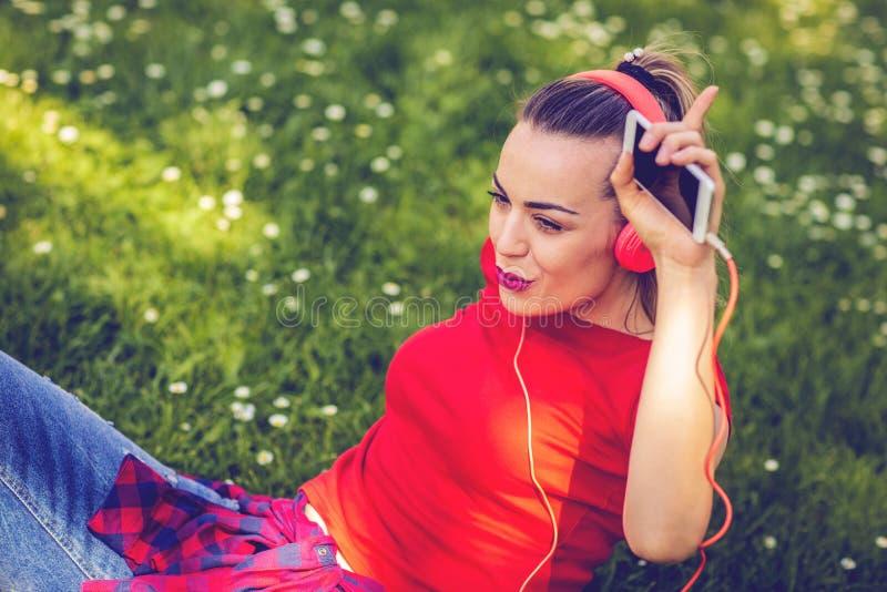 有耳机和智能手机的愉快的妇女听到音乐的  免版税库存照片