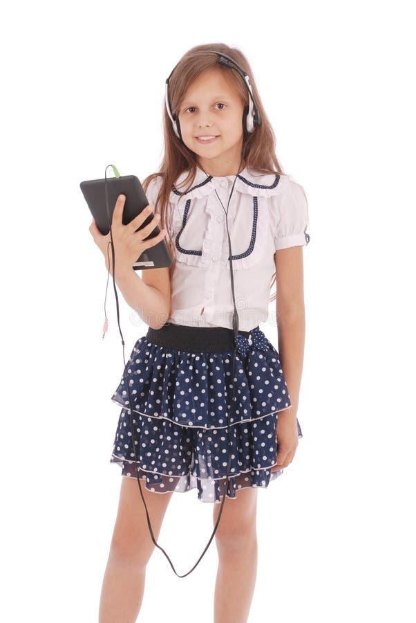 有耳机和片剂个人计算机的美丽的逗人喜爱的愉快的女孩 免版税库存图片