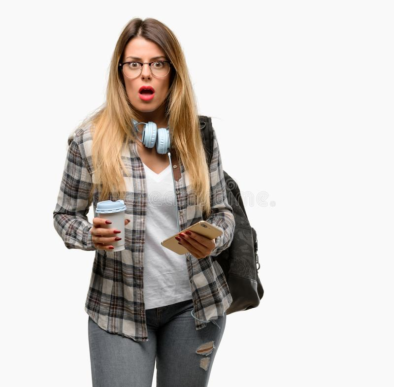 有耳机和背包的年轻学生妇女 库存图片