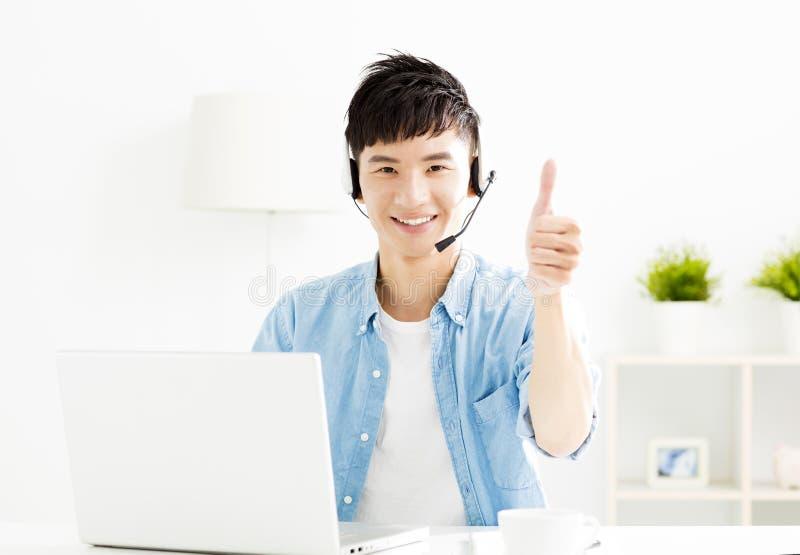 有耳机和膝上型计算机的年轻人 免版税库存图片
