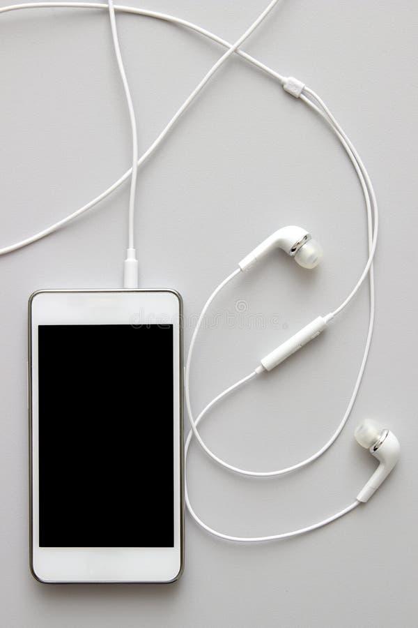 有耳机和被隔绝的屏幕的白色巧妙的电话在桌上 免版税图库摄影