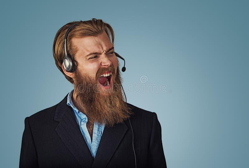 有耳机工作的人作为呼喊充满愤怒的操作员 库存照片
