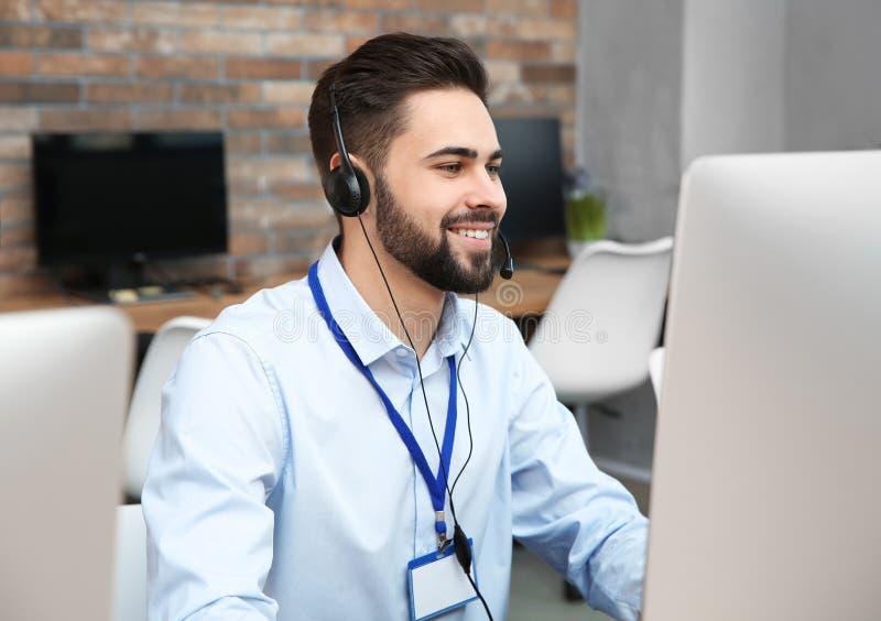 有耳机工作的技术支持操作员 免版税库存照片
