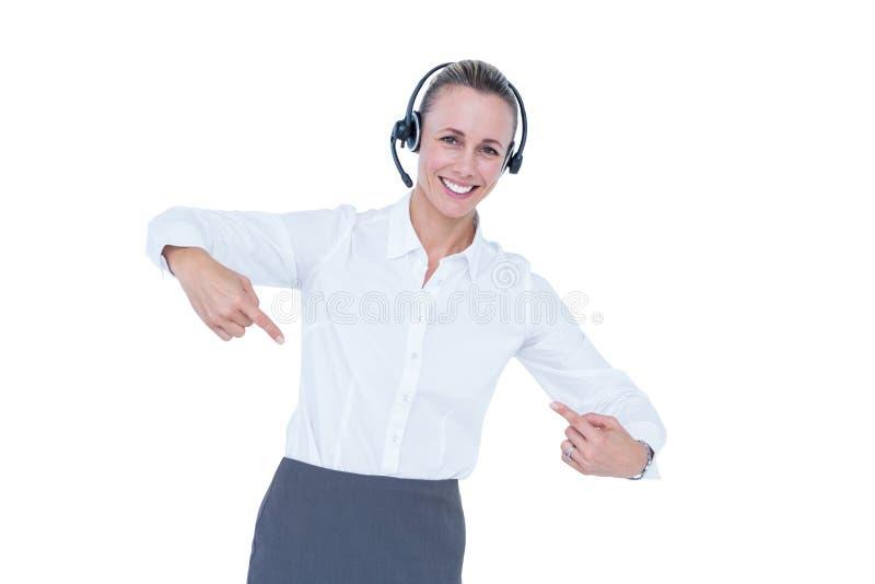 有耳机指向的微笑的女实业家 免版税库存照片