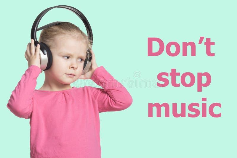 有耳机的一个小女孩听到音乐的 孤立 题字不停止音乐 免版税图库摄影