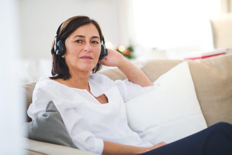 有耳机的一名资深妇女在家听到音乐的在圣诞节时间 免版税库存图片