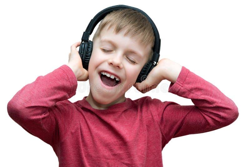 有耳机的七岁的男孩唱歌在白色的 免版税图库摄影