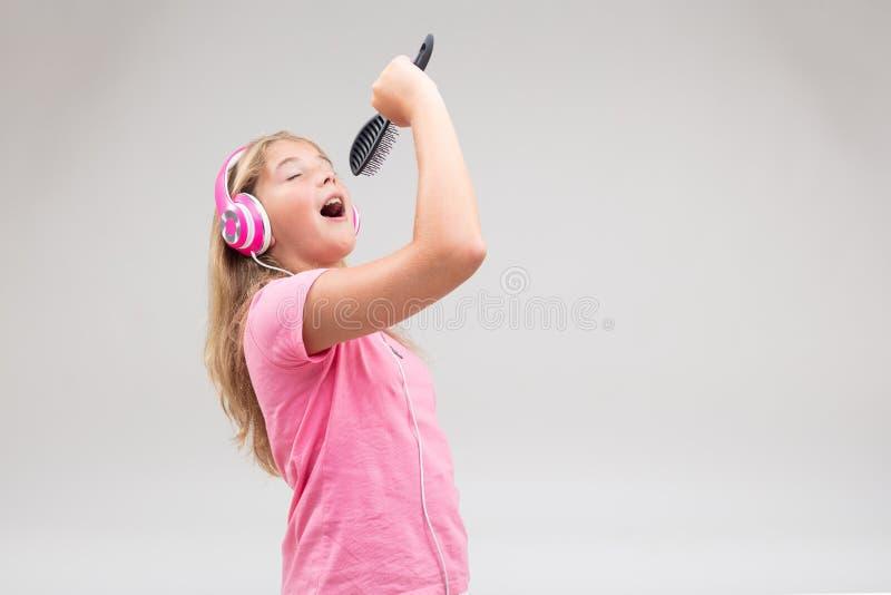 有耳机的假装的女孩是歌手 免版税库存图片