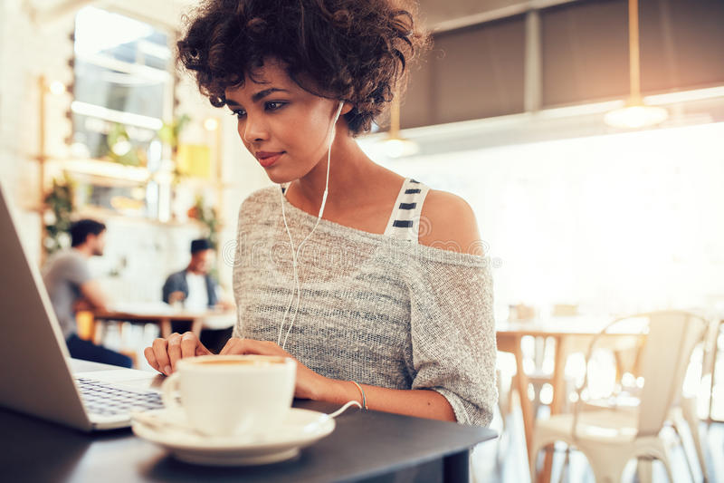 有耳机的可爱的少妇使用在咖啡馆的膝上型计算机 库存图片