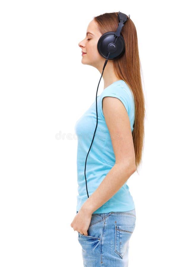 有耳机的听到音乐的少妇档案  免版税库存图片