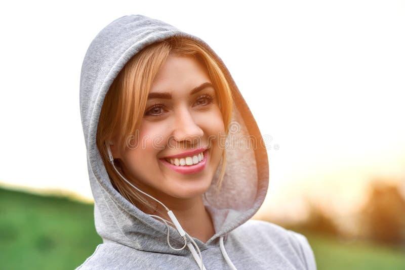 有耳机的听年轻白种人女性的慢跑者音乐 免版税库存图片