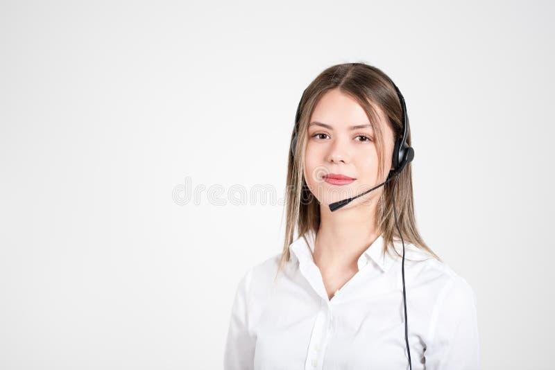 有耳机的女性咨询的经理在轻的背景 免版税图库摄影