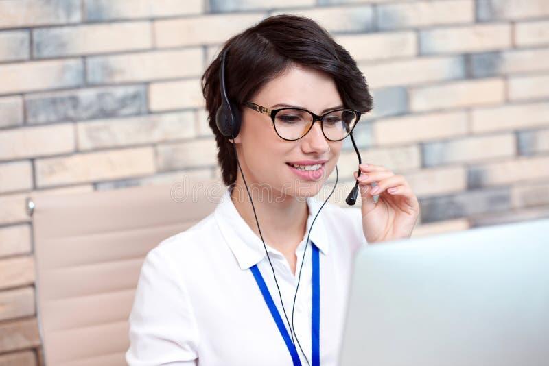 有耳机的女性技术支持操作员在办公室 图库摄影