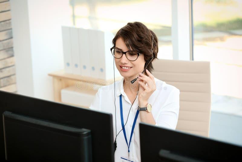 有耳机的女性技术支持操作员在办公室 库存照片