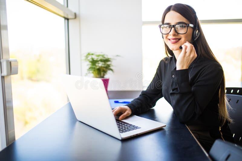 有耳机的女性用户支持操作员和微笑在办公室 免版税图库摄影