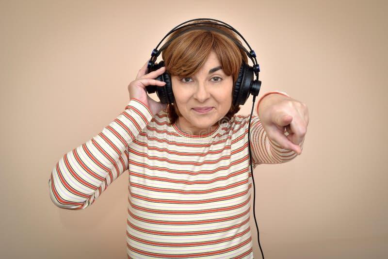 有耳机的妇女把她的食指指向的照相机 免版税图库摄影