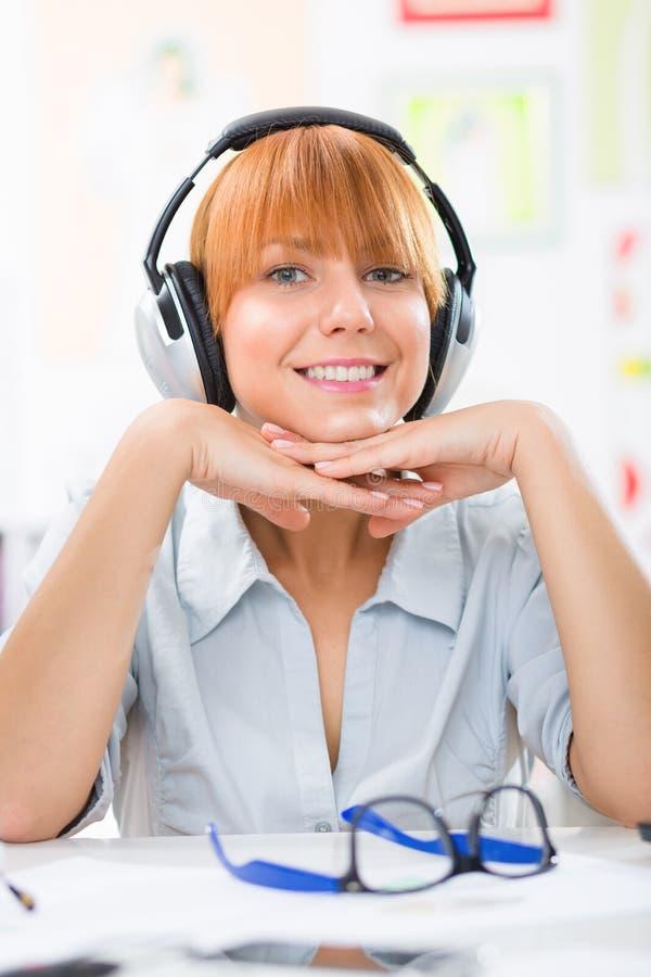 有耳机的少妇听音乐和看照相机的 免版税库存图片