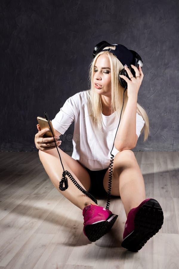有耳机的少妇坐地板在墙壁附近 库存照片
