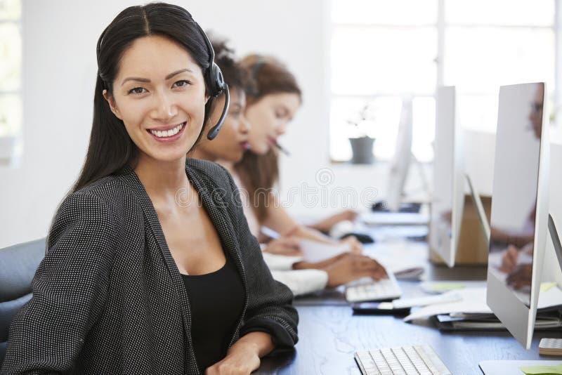 有耳机的年轻亚裔妇女微笑对照相机的在办公室 免版税库存照片