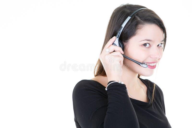 有耳机的年轻女人与旁边后面拷贝空间的回答的电话的 免版税库存图片