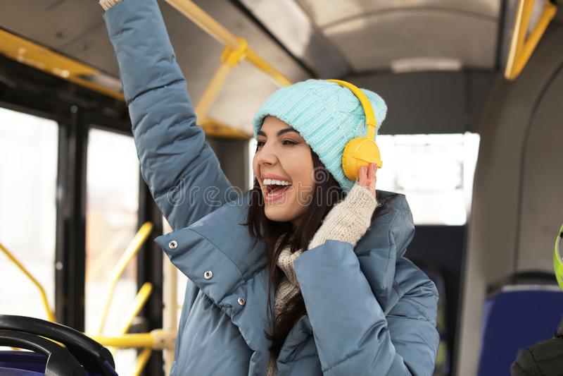 有耳机的年轻女人在公共交通工具 免版税库存照片
