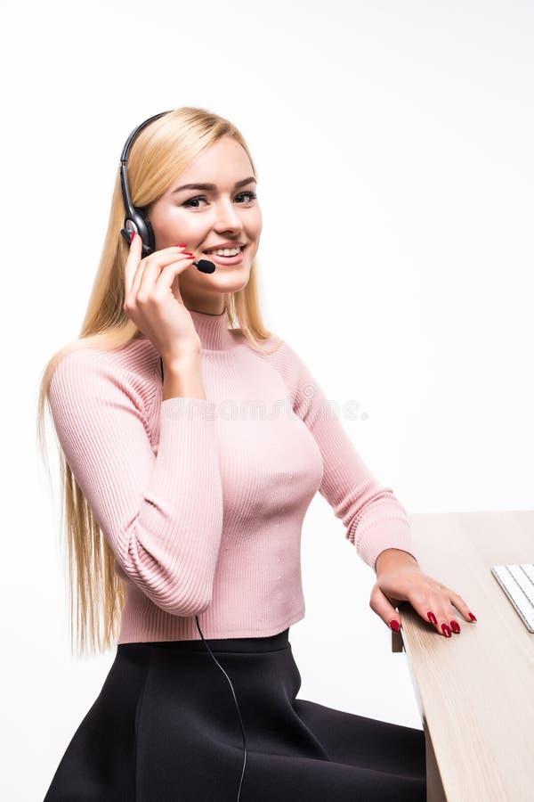 有耳机的微笑对照相机的女性操作员画象在电话中心在白色 免版税库存照片