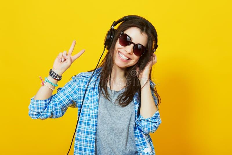 有耳机的微笑的十几岁的女孩显示和平姿态 免版税库存图片
