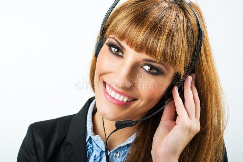 有耳机的微笑的可爱的妇女 库存照片