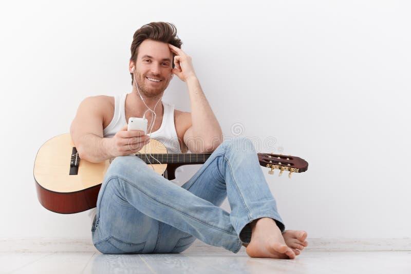 有耳机的愉快的吉他弹奏者 免版税图库摄影