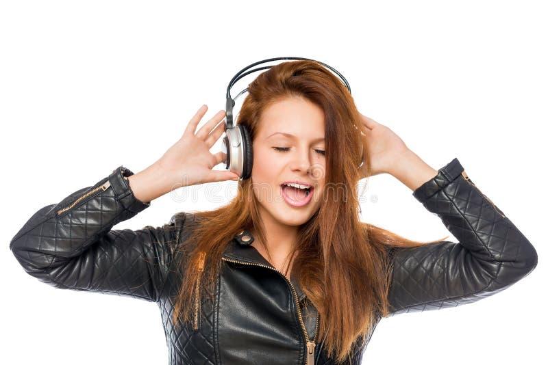 有耳机的愉快的女孩听对和唱岩石的 库存图片