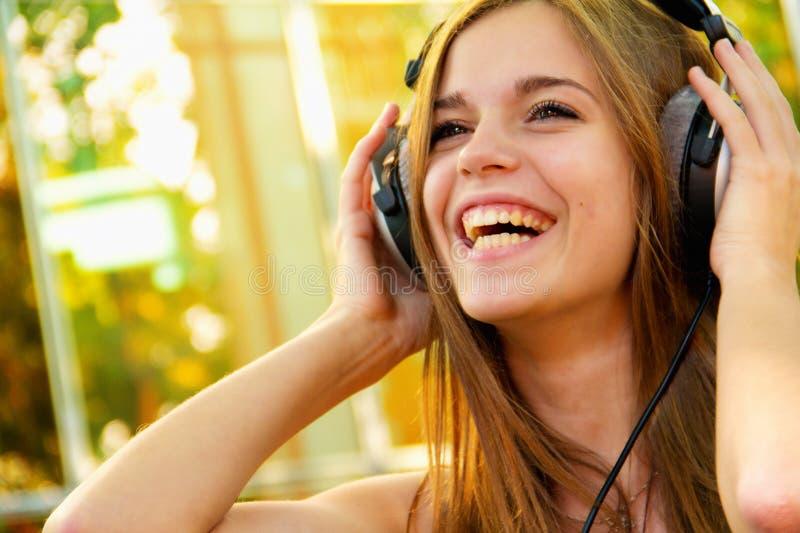 有耳机的愉快的妇女  免版税库存图片