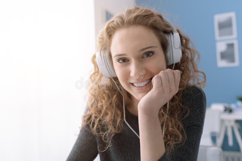 有耳机的愉快的微笑的卷曲女孩 库存照片