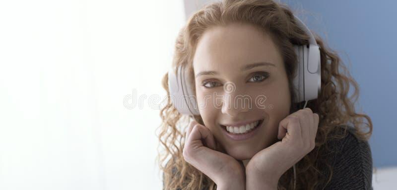 有耳机的愉快的微笑的卷曲女孩 免版税库存图片