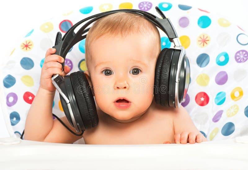 有耳机的愉快的婴孩听到音乐的 库存图片