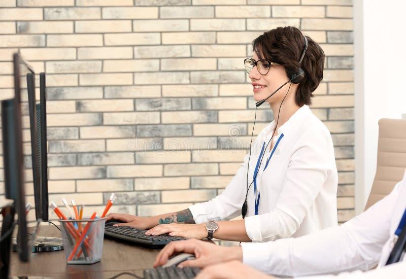 有耳机的技术支持操作员在办公室 免版税图库摄影