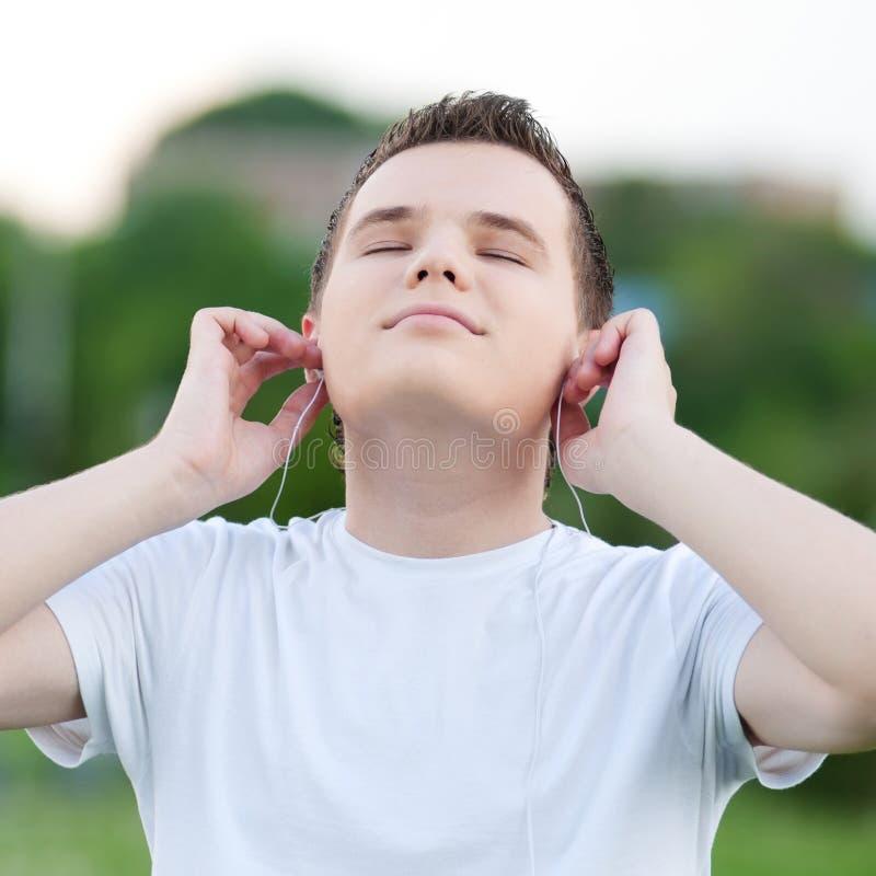 有耳机的新可爱的人 库存图片