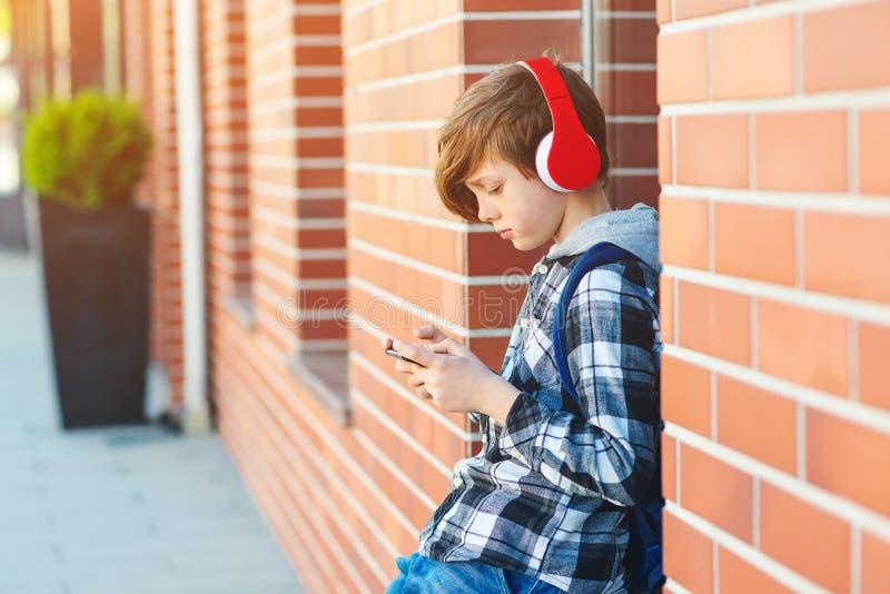 有耳机的时髦的孩子男孩使用在城市街道的电话 年轻男孩打网络游戏全部在智能手机 青春期前的男孩听 免版税库存照片