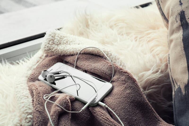 有耳机的智能手机在软的格子花呢披肩 图库摄影
