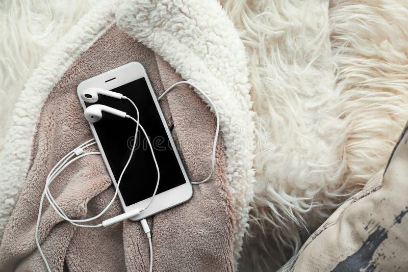 有耳机的智能手机在软的格子花呢披肩 免版税库存图片