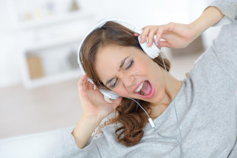 有耳机的滑稽的少妇唱歌和听到音乐的 免版税库存照片