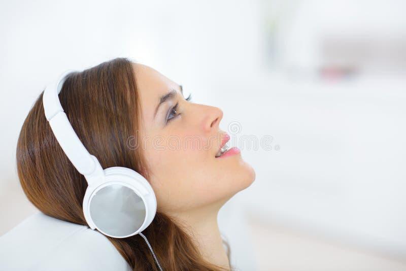 有耳机的特写镜头画象可爱的年轻女性 免版税图库摄影