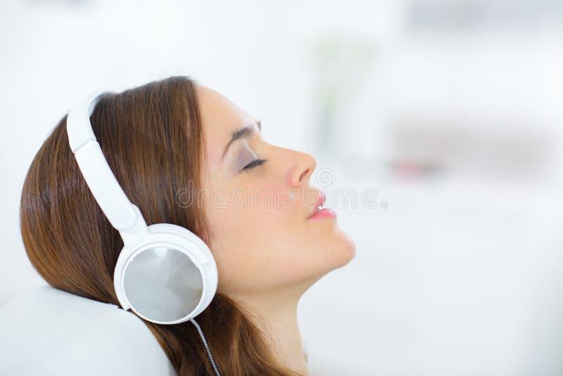 有耳机的特写镜头画象可爱的年轻女性 免版税库存照片