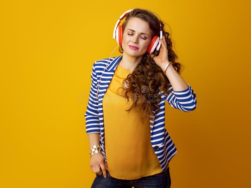 有耳机的现代妇女听到音乐的 免版税库存照片