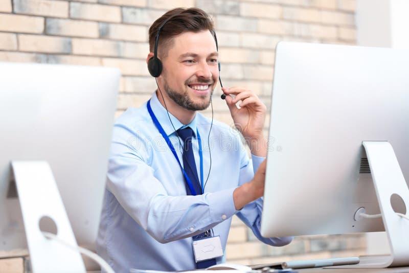 有耳机的男性技术支持操作员在办公室 免版税图库摄影