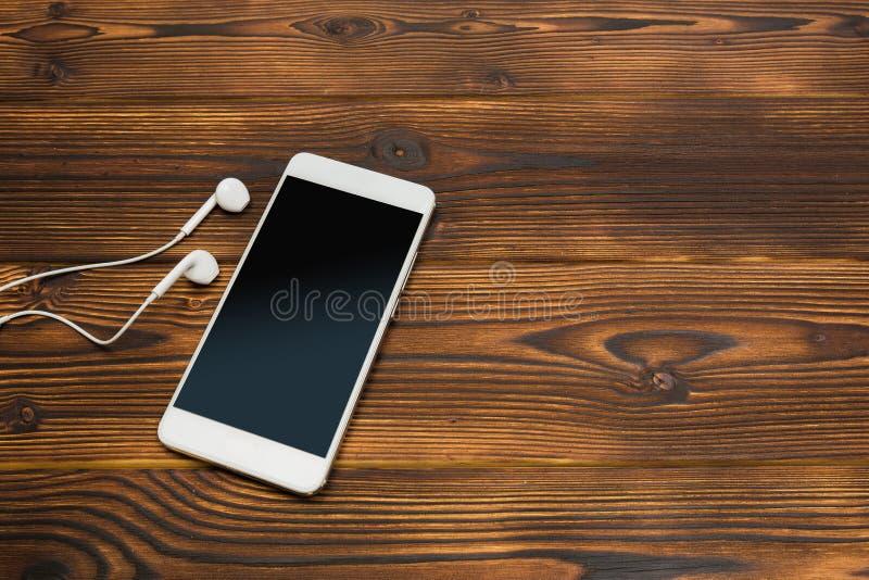 有耳机的白色智能手机在木背景 库存照片