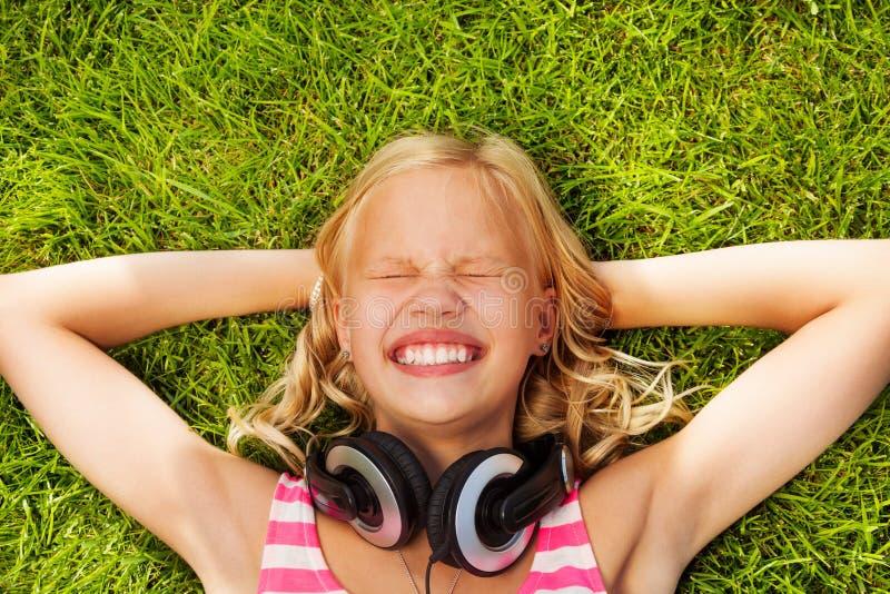 有耳机的笑的女孩在绿草放置 免版税库存照片
