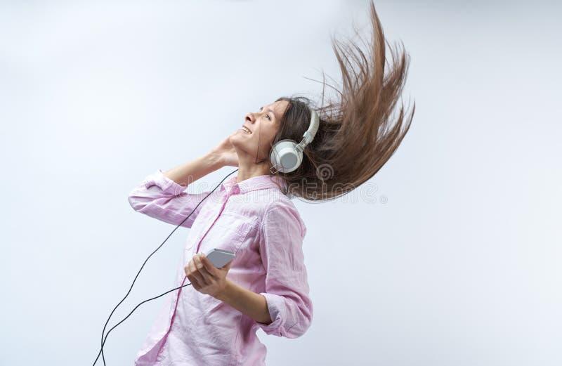 有耳机的美丽的女孩在一白色背景微笑和悬而未决她的头发 库存图片