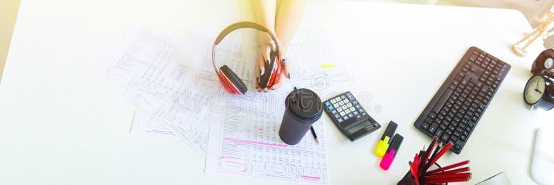 有耳机的美丽的女孩在手上在办公室坐在桌上 免版税库存照片